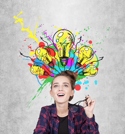 Close up of a geeky teen girl having an aha moment sitting near a concrete wall with many light bulbs and color splashes