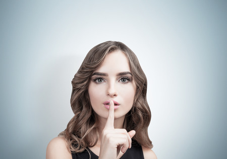 Close up of a young European woman with wavy hair making a hush sign. Gray background. Concept of conspiracy and keeping a secret Stock Photo