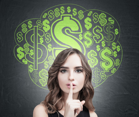 Close up of a young European woman with wavy hair making a hush sign. Blackboard background with a green dollar sign cloud sketch on it. Reklamní fotografie