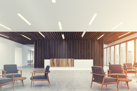 Corner of a white and light wooden reception counter is standing in a black office lobby with wooden decoration elements. Armchairs in an empty hall. 3d rendering mock up toned image Stock Photo