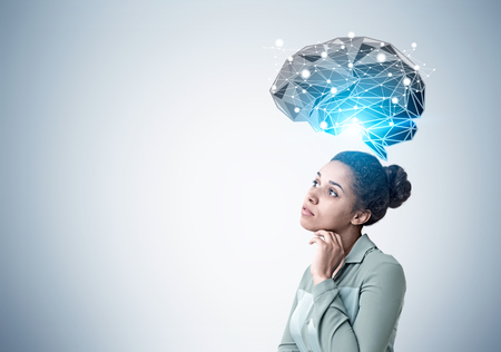 Side view of a pensive African American woman standing near a gray wall with a black brain hologram shining with a blue light. Mock up Stock Photo