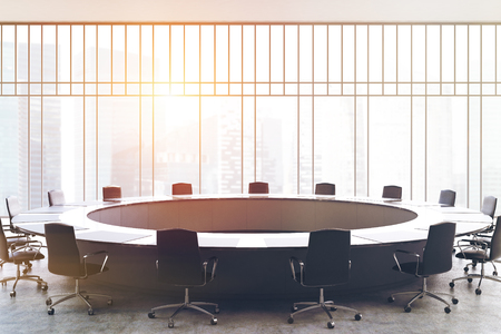 round chairs: Meeting room interior with a large black round table, office chairs standing around it and a window with a magnificent view. 3d rendering mock up toned image Stock Photo