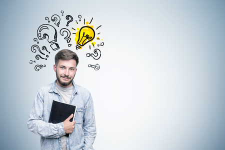 he is different: Portrait of a bearded young man in a jeans shirt. He is holding a black notebook and standing near a gray wall with a yellow light bulb surrounded by question marks of different size. Mock up