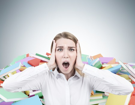 bibliomania: Close up of a blond businesswoman wearing a white shirt and screaming in terror. There are piles of books of different color behind her. Mock up