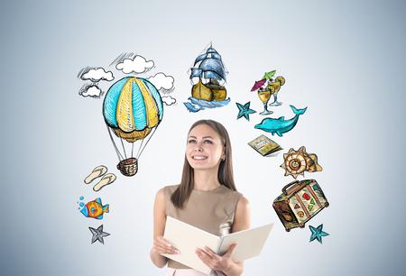 Retrato de una empresaria joven sonriente sosteniendo un gran cuaderno y de pie cerca de una pared gris con bocetos de viaje y medios de transporte históricos. Foto de archivo
