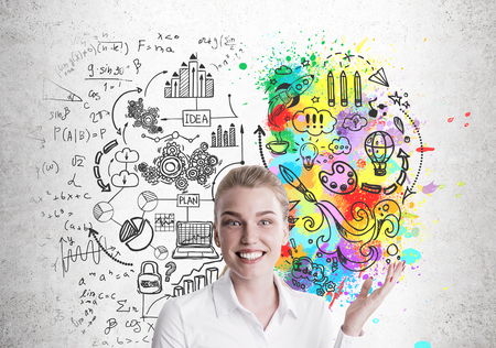 Cheerful blond businesswoman is standing near a concrete wall with a colorful brain sketch and business icons on it. Stock Photo