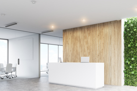 Corner of a white reception desk with two laptops standing on it in front of a wooden office wall. There is a grass wall seen through a wall opening. 3d rendering, mock up Stock Photo