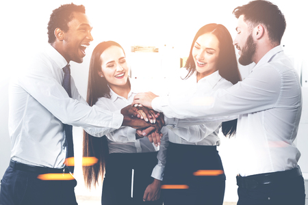 Members of a diverse business team are standing in a circle with their hands together teaming up. They are having fun and being successful. Toned image Stock Photo