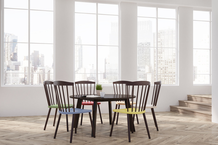 round chairs: Dining room interior with white walls, tall windows and a round table with wooden chairs of different colors near it near it. Cityscape. 3d rendering mock up