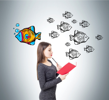 Side view of young woman wearing a dress and reading a red book standing near a gray wall with fish. One of them is bright and swimming to a different direction. Concept of leadership