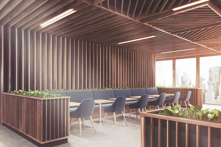 Side view of a modern cafe or a coffee shop interior with wooden walls, panoramic windows and dark blue armchairs standing near square wooden tables. 3d rendering mock up toned image Stock Photo