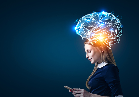 Side view of a blond businesswoman looking at her smartphone screen standing near a dark blue wall. There is a large blue brain hologram around her head. Mock up