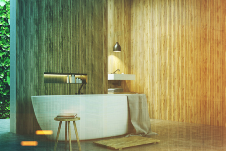 Eco bathroom corner with narrow windows, green shrubbery is seen through them. There is a sink next to a white tub standing near a wooden wall. 3d rendering mock up toned image Reklamní fotografie