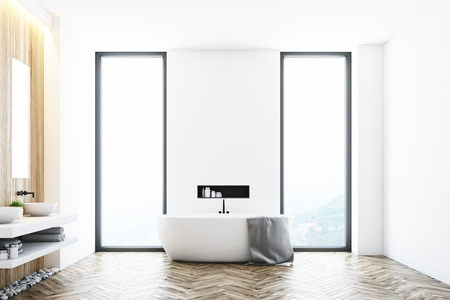 White modern bathroom interior with a white tub standing near a window, a large towel hanging on its side and a shelf with cleaning products in the wall. 3d rendering, mock up Stock Photo