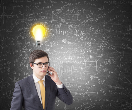 he: Young businessman wearing glasses, a suit and a yellow tie. He is talking on his smartphone near a blackboard with formulas. There is a light bulb above his head. Mock up