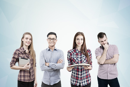 associate: Two women and two men are standing together near a gray wall. One of them is holding an open book and a tablet. Brainstorming. Mock up Stock Photo
