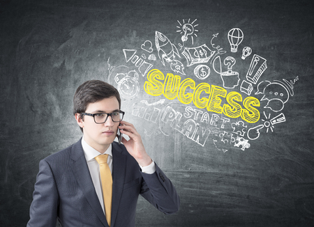 he: Young businessman wearing glasses, a suit and a yellow tie. He is talking on his smartphone near a blackboard with a white and yellow succress sketch on it.