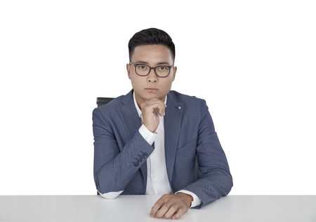 centered: Isolated portrait of a young Asian businessman wearing glasses and a blue suit and sitting at a table. Concept of decision making.