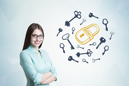 looking at viewer: Young businesswoman wearing glasses and a blueish shirt standing with crossed arms and smiling while looking at the viewer. Gray wall, keys around a padlock Stock Photo