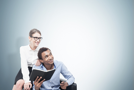 loveliness: Portrait of a smiling African American man wearing a blue shirt and a young blond woman wearing glasses and sitting on a leather armchair near him. Mock up Stock Photo