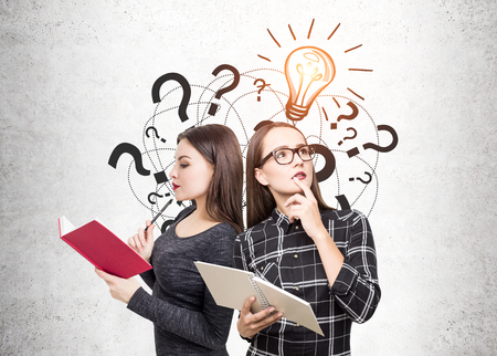 Side view of a young woman wearing a gray sweater and her nerd colleague in a checkered shirt and glasses. They are holding open books and thinking. Concrete, question marks and a light bulb