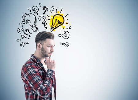 t bulb: Side view of a bearded young man in a checkered shirt and a white T shirt thinking near a gray wall with many question marks and a yellow light bulb drawn on it. Mock up