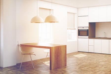 modern interior: Close up of a white kitchen interior with white wooden floor, minimalist table, transparent chairs and countertops with a built in oven. 3d rendering mock up toned image