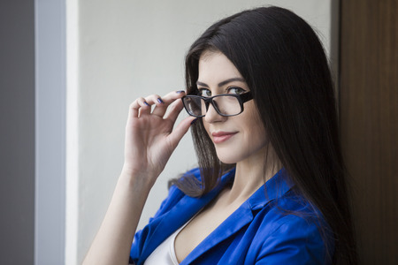 Portrait of a young black haired businesswoman wearing glasses and looking at the viewer with an interest.