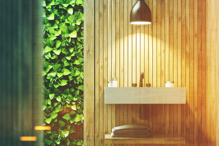 Eco bathroom interior with a narrow window, green shrubbery is seen through it. There is a sink hanging on a wooden wall. 3d rendering mock up toned image