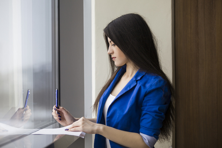 Side view of a young woman lith long dark hair wearing a blue suit and writing on a paper standing near a window