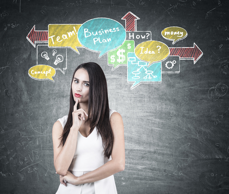 theorize: Portrait of a pensive businesswoman with dark hair. She is wearing a white shirt and standing near a blackboard with a colorful business planning schemes. Stock Photo