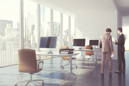 Businessmen in a modern office with white computer tables, brown office chairs and concrete floor. 3d rendering mock up toned image Reklamní fotografie