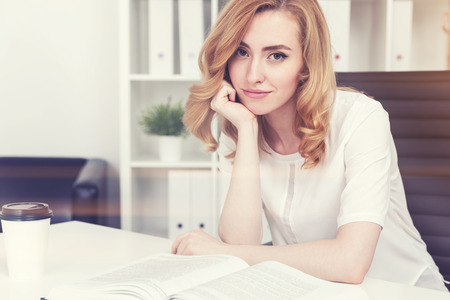Portrait of a stunningly beautiful young red haired company employee sitting at her workplace in a white office and looking at the viewer as if listening to every word they are saying. Toned image Stock Photo