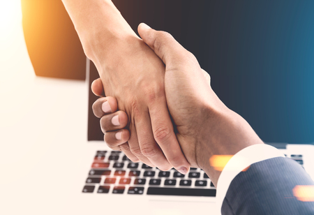 african american handshake: Close up of an African American man and a woman shaking hands. Office background. Concept of business partnership. Toned image.