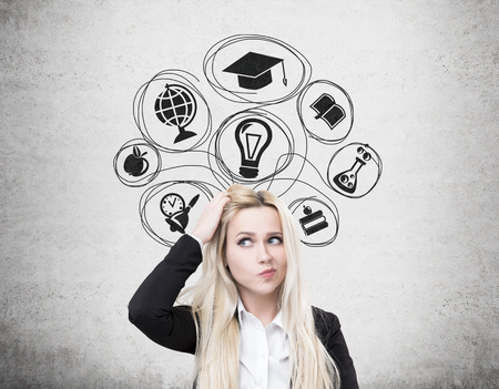 Portrait of a confused blond woman standing near a concrete wall with education icons and scratching her head. Stock Photo