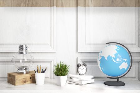 Interior of a kids room with a white wooden table, a wooden wall, an oil lamp, an alarm clock and a globe Stock Photo