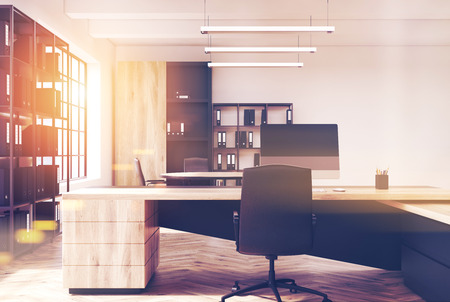 ceo: Sunlit CEO office interior with a wooden table and bookcases. There are office lamps and white walls. Loft. Computer on a desk. 3d rendering mock up toned image Stock Photo