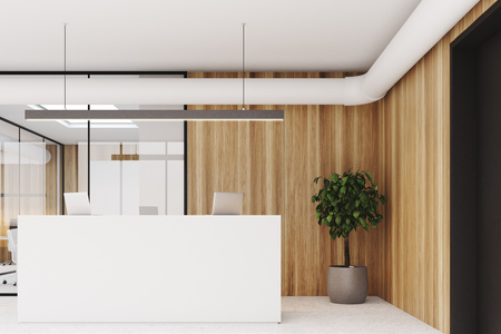 Wooden wall office interior with a concrete floor, glass walls, a tree in a pot and a white reception counter with laptops on it. 3d rendering mock up