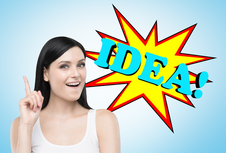 Portrait of a happy black haired woman wearing a white tank top and standing with a finger pointing up and standing near a blue wall with a comic book style idea! sketch Stock Photo