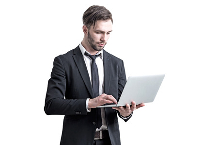 Isolated portrait of a young and handsome bearded businessman in a suit holding a laptop and working. Concept of success. Stock Photo
