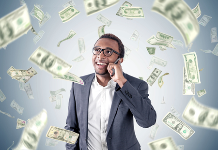 L'homme d'affaires afro-américain dans un costume parle sur un téléphone intelligent tout en se tenant près d'un mur gris avec des billets en dollars qui tombent autour de lui. Banque d'images - 82159525