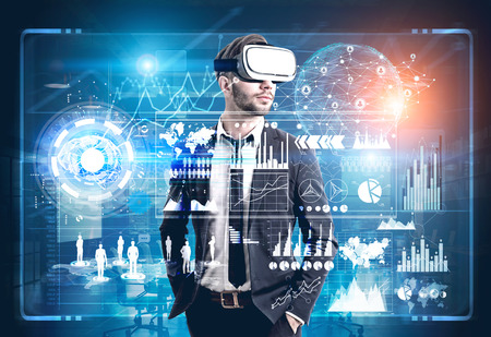 double game: Front view of a bearded man wearing a suit and VR glasses and standing in a futuristic environment. HUD and graphs behind him. Toned image double exposure. Elements of this image furnished by NASA