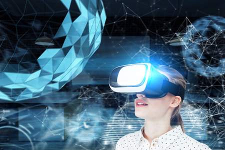 Blond girl in a white dotted blouse wearing VR glasses and standing against a blue background with a polygonal orb hologram Toned image double exposure