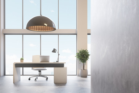 Loft CEO office with a gray wall, panoramic windows, a modern computer table with a laptop and a lamp on it. A tree in a pot. 3d rendering mock up Stockfoto