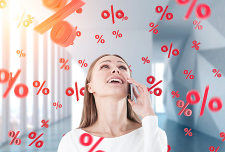 Portrait of a happy, young and beautiful businesswoman talking on a smartphone and looking upwards. Office background. Percent signs. Toned image double exposrue Stock Photo