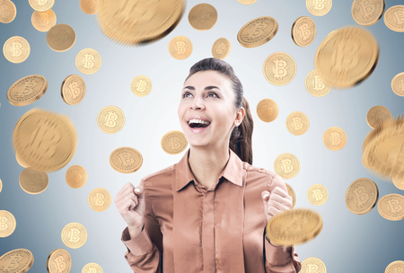 Portrait of a happy young woman wearing a brown blouse and standing under a bitcoin rain near a gray wall. Stockfoto