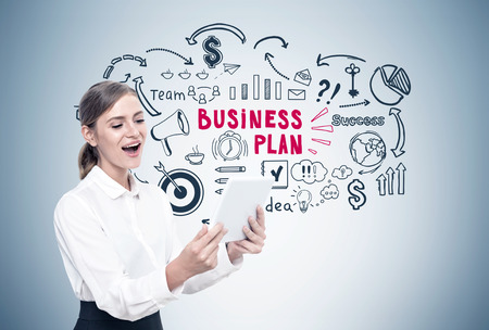 Happy blond businesswoman looking at her tablet screen and screaming with joy. Gray wall with a black and red business plan sketch on it. Stock Photo