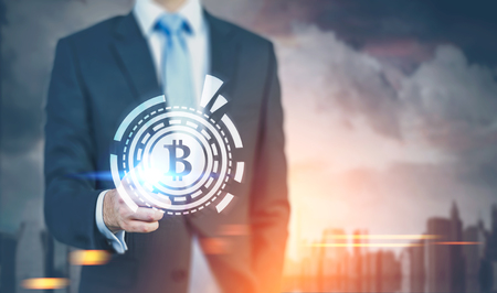 Close up, businessman interacting with a large bitcoin sign inside an HUD in front of a world map. Cityscape background. Toned image double exposure mock up.