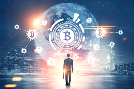 Rear view of a businessman with a suitcase looking at a bitcoin network with a bitcoin sign inside an HUD, world map. Night city. Toned image double exposure Elements of this image furnished by NASA Фото со стока