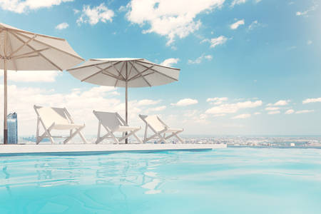 Three white deck chairs are standing under beach umbrellas near a swimming pool. A blue sky with clouds is above them. Side view. 3d rendering mock up Stock Photo